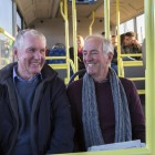 Two senior men smiling and talking on the bus. There are other people sitting on the bus in the background.