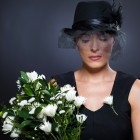 sad young widow with black mourning hat and flowers